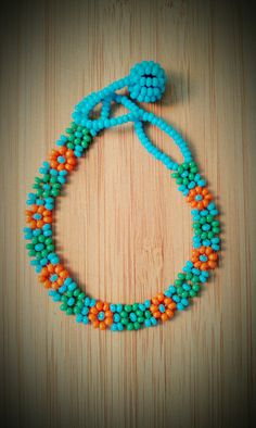 Beaded blue, green, and orange daisy chain bracelet with beaded loop and ball closure. $12.00, via Etsy.