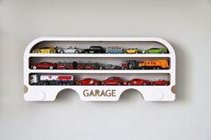 """Polička GARAGE Nová polička pro malá auta a autíčka, třeba do vleku za našíAutopoličku. Je vyrobena z několika vrstev vlnité lepenky (EB vlna) a bočního bílého kartónu (mikrovlna). Bílá krycí vrstva je pouze z jedné strany, z druhé zůstává hnědý karton. Levá nebo pravá varianta. Tato polička vychází z naší pojízdné poličky """"Jezdím ekologicky"""", která pojme ..."""