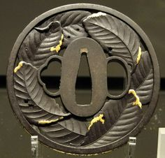 Tsuba sword guard decorated with persimmon leaves