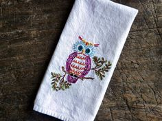 Brand new 100% cotton tea towel/dishtowel/towel. Measures 28 inches x 18 inches and is natural white with red stripes on the edges. I hand-embroidered this towel with a wonderful retro design of a cute owl. Bright and cheerful in shades of berry, orange, teal, yellow, red and green, this quirky little guy would look great in your kitchen or bathroom, but is also completely practical to actually USE. I use my hand-embroidered towels in the powder room...they hold up really well t...