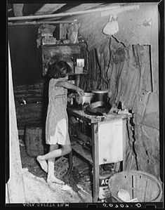 Jan 1939 Oldest child of migrant packinghouse worker's family from Tennessee fixing supper. Her mother and father both work during the day and sometimes until two and three in the morning, leaving the children alone. Belle Glade, Florida. . Photogrphed by Marion Post Wolcott.