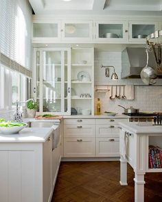 glassfront sliding kitchen cabinets in offwhite ivory light gray honed quartz countertops subway tiles backsplash and stainless steel apron sink