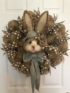 This large natural colored poly jute burlap mesh Easter wreath with decorative bunny rabbit face and polka dot accent ribbon will spice up any door/room this holiday season. The natural Easter bunny rabbit face is made of layers of natural sisal grasses. Two large wired ears, that can be shaped anyway you like, stand above a blue burlap floppy hat and blue burlap bow around the neck. A burlap rose adorns her hat. Measures approximately 24 inches. Ready for immediate shipping. Thanks for ...