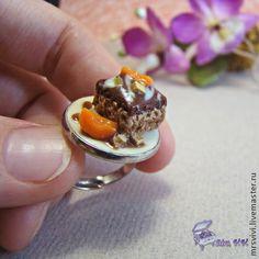 Кольцо Персик в шоколаде. Колечко с регулируемой основой в виде миниатюрного шоколадного пирожного, украшенного сочными дольками персика и поданного на перламутровом блюдечке..