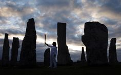 Kirsty Wade holds the Olympic Flame at the Calanais Standing Stones in Callanish, UK.  Photo by The Atlantic.