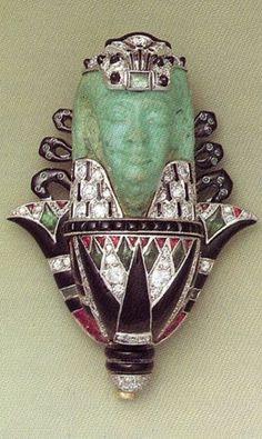 Faience, diamond, emerald, ruby, onyx and gold 'Dieu sur une fleur de lotus' brooch, by Cartier, circa 1925. Collection Cartier Genève. #Cartier #EgyptianRevival #ArtDeco #brooch