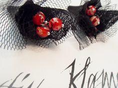 http://de.dawanda.com/product/36144761-Ohrhaenger-mit-Millefiori Die versilberten Brisuren haben einen schwarzen Blütenanhänger mit je 3 Millefiori Perlen, Baumwolle und Tüll
