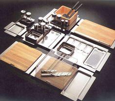 """En 1971 se crea el """"Programa 8"""", conjunto de objetos modulares para mesa con formas de base cuadrada o rectangular, muy difíciles de producir en acero, es por eso que se expande al plástico, a la madera (1989); al vidrio, a la porcelana y a la cerámica (1992).   En la actualidad la misión es traducir la investigación de la más avanzada calidad cultural, estética, ejecutiva y funcional en la producción industrial en serie afinando el uso de materiales y formas."""