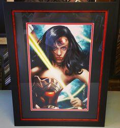 It's Wonder Woman! Framed with two acid-free mats, conservation glass and @bellaprisma stacked inside a black wood frame! #art #pictureframing #customframing #denver #colorado #wonderwoman