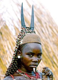 Africa | Somba initiate with antelope horns on her straw-woven cap and a white stone jutting down from a hole under her lower lip.  Atakora Mountains near Boukombe, Benin. | © Victor Englebert
