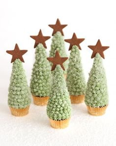 """Christmas Tree Cupcakes -- Serve this snowy dessert this holiday season. Cupcakes are shaped like trees, covered with Snowy Frosting, and sprinkled with sanding sugar. Save some sugar to create beds of """"snow"""" for serving. If you like, you can also make mini gingerbread stars to decorate the tops of the trees."""