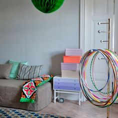 As featured in Marie Claire Maison. A guest room with a daybed cover in Raffia Textured cotton Sage Brown. Fun details such as the hoola hoops, coloured storage boxes and vibrant throw give the room a welcoming and playful feel.