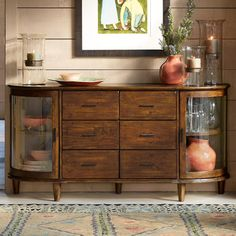"""PIONEER PARLOR CONSOLE--Like our perennially popular demi-lune buffet design, this updated reclaimed pine buffet table combines rugged good looks with refined details, such as curving glass doors and sleek, hand-wrought iron hardware. It's bench-made with tongue and groove joinery of solid FSC-Certified® reclaimed pine that still displays the rustic characteristics of its former uses. Six drawers, single fixed shelf on each end. Imported. 67""""W x 18""""D x 34""""H."""