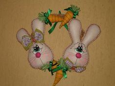 Guirlanda em capim, com cenouras e coelhos em feltro.