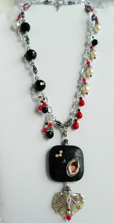 """My second entry for the Bead Soup Blog Party.  I used one half of a toggle clasp to create a frame for the Geisha girl picture, then sealed it in Resin.  The focal is a Black Obsidian semi-precious stone, and the leaf is pure silver.  These pieces were part of the """"Soup"""" that my Partner sent to me.  Kate from Mulligan Stew Jewelry."""