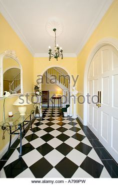 black and white tiles in this hallway really brighten up this room, notice that the yellow is the dominant colour and the brilliant bright white is a highlight colour.  The end result is bright and sunny and happy.