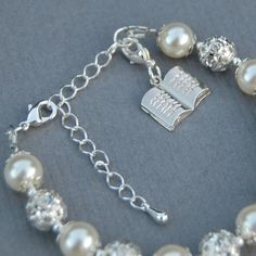 Pearls and sparkling rhinestones make this bracelet a lovely communion, confirmation or religious gift. The silver plate Holy Bible charm measures approx. 1/2 x 5/8 (1.3cm x 1.5cm)  This bracelet is not suitable for children under 3 years of age and children under 5 years should be supervised when wearing it. PLEASE NOTE - I am in the UK so please allow extra time for international shipping  The bracelet is finished with a silver lobster clasp and 2/5cm extension chain. Please ...