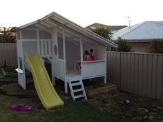 An all white cubby house with a bright yellow slide. #cubby #cubbyhouse #cubbies #kidsplay #play #imaginationplay #outdoorplay
