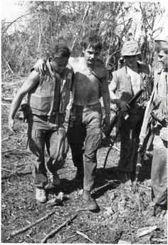 """""""Buddy Aid"""", June 1968 The caption reads """"A Corpsman attached to the 1st Battalion, 27th Marines helps a wounded Leatherneck to a helicopter landing zone so he can be evacuated for medical aid. They were participating in a recent operation southwest of DaNang."""""""