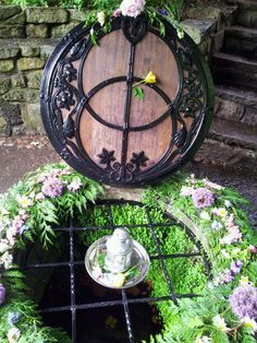 Chalice Well Glastonbury the Day After Summer Solstice; Dressed with Roses and Lilac Blossom, Large Headed Purple Alysium and Dog Daisies...By Artist Unknown...