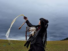 shaman offering | Picture of a novice shaman making an offering of milk to the spirits