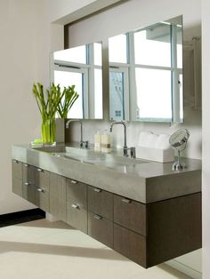 Upscale Urban Vanity - The stunning double vanity floats against the bathroom wall slab-panel cabinets supporting a poured-concrete countertop with an integrated trough sink that accommodates two faucets. A pair of generous mirrors reflect the spectacular city views while capturing a bounty of natural light.
