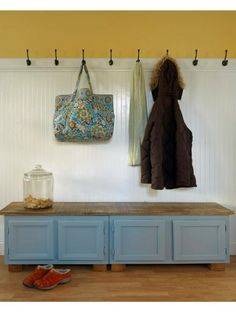 Two kitchen cabinets that normally go above a refrigerator were turned into a handy entryway bench and shoe storage. Design by Joanne Palmisano