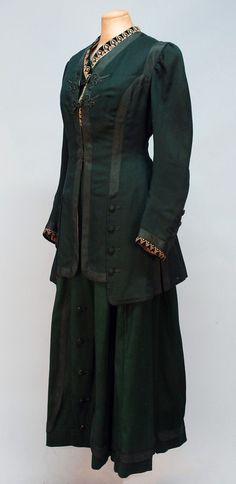 HERRINGBONE WEAVE WALKING SUIT, c. 1905. Hunter green wool having long jacket trimmed in green passementerie, braid and faux buttons with faux velvet vest with cream embroidery, weighted hem, lined in cream silk satin, pleated skirt with decorated front panel. Front