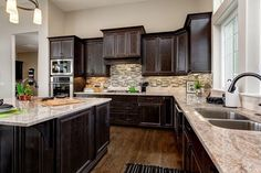 Dark cabinetry can be right at home in a lighter-colored kitchen. The key: dark metal fixtures and a backsplash pattern that ties it all together.