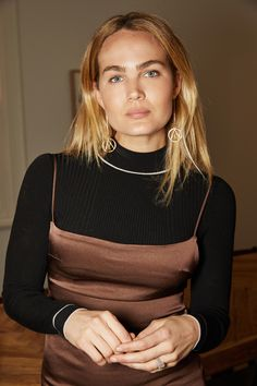 Brooke Testoni wearing Hera Saabi earrings, Paris Georgia Basics dress and Misha Nonoo turtleneck at home