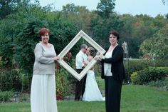 Daughters 1940's Vintage Style Wedding: Mothers of Bride and Groom holding a vintage Picture frame framing  the bride and groom .