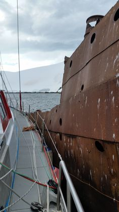 """We had a tricky time leaving our mooring.  The GRIBs said 5k of wind - but we had 30k of katabatic winds off the mountains pinning us to the hulk.  Took 4 crew on the hulk and rocks and two in the dinghy acting as a tug to get clear """"cleanly"""".  Was strange standing on the hulk as the boat pulled away.  A few hours before Buzz and Thomas used the dinghy to move a bergie bit that drifted into our bow - a bit that likely weighed 15-20 tons."""