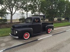 Ford F1 pickup in a perfectly smooth flat black paint job and rolling on red wheels.