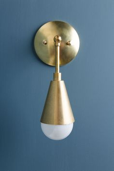 This wall sconce with cone is made with all brass and can be adjusted 180 degrees. The sconce is 5 inches from the wall and hangs 7 inches down.