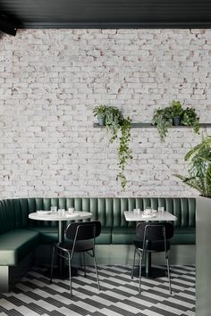 An emerald banquette winds around a peripheral wall, tying in with the green colour scheme. The base of each seating booth has then been inlaid with slim forest-green and sage-tone tiles.