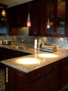 dark cabinets, light countertop, colorgul backsplash