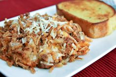Baked Spaghetti w/Cream Cheese & French Fried Onions  Ingredients  8 ounces uncooked spaghetti  1 pound ground beef  1 (24 oz.) jar spaghetti sauce  1 tablespoon butter  1/3 cup chopped onion  2 cloves garlic, minced  8 ounces cream cheese, softened  1/3 cup water  Salt and pepper, to taste  1 cup shredded mozzarella cheese  1/2 cup fresh grated Parmesan cheese  French Fried Onions (small can)