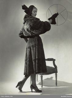 Kvinna i mörk päls med markerad midja och vida ärmar. Mörk hatt med 67ddb6eaf55a6