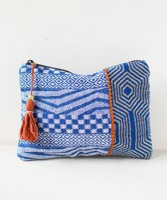 """Pack your essentials in this geometric inspired, indigo embroidered clutch with orange tassel zipper closure Approx. 9x7"""""""