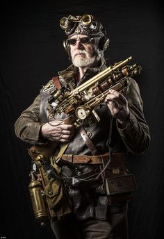 A man dressed as fantasy character Thaddeus poses for a photograph at the festival. Steampunk comes from science fiction and incorporates Victorian fashion with steam-powered mechanics. The steampunk is kitted out in a leather hat with brass ear protectors and is carrying a 'gun' made out of brass and wood. He is cladded in brown leather and has a metal canister strapped to his waist