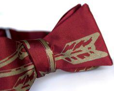 "Burgundy Arrows bow tie, freestyle. Silkscreened necktie, antique brass print. ""Quiver.""  $40"