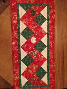 Entry 16  Nancy S Christmas runner using pattern from http://vickisfabriccreations.blogspot.com/p/free-pattern-project-downloads.html . After making the runner embroideries from the following sets were used, 776, 634, 1272, 175, 1415, and 1079. The quilting design was from 355.