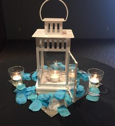 (12) available. White lantern on a big square mirror with aqua foe flower petals at the base with tealights flanking either side, and one inside the lantern!