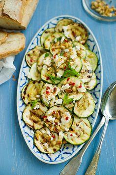 Pinienkerne bei Umluft 160° C etwa 10 Minuten rösten. Zucchini in ca. 5 mm dicke Scheiben schneiden, mit Salz und Pfeffer würzen, mit Olivenöl und der fein gehackten Knoblauchzehe mischen. Unter Wenden in einer Grillpfanne 3-5 Minuten braten. Mit der fein gehackten Chilischote und etwa 1 EL Zitronenschalenabrieb mischen. Zucchini auf einer Platte anrichten, Feta, Minze und Pinienkerne darübers ...