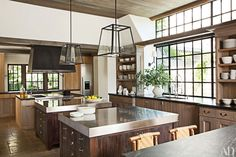 In the kitchen, sconces from Urban Electric Co. illuminate the sink areas, and pendant lights designed by Rela are installed over the stainless-steel islands; Thermador refrigerator and freezer columns (one unseen) bookend the far counter, and the range is by Wolf.