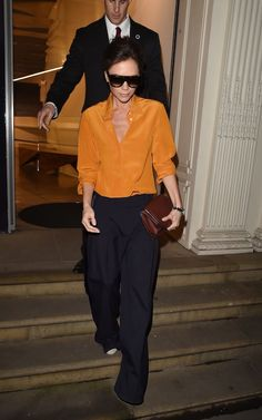 Known for her polished look, minimal accessories and clever knack for showing how to style her eponymous fashion line at every opportunity, there's no doubt that Victoria Beckham is a modern style icon from whom we can all take a few sartorial notes. Fashion Line, Fashion Looks, Victoria Beckham Style, Orange Shirt, Shirt Outfit, Knitwear, Cool Style, Celebrity Style, Style Inspiration