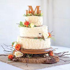 Rustieke bruidstaart met verse oranje bloemen en houten initalen als taarttopper