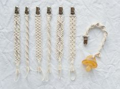 Handmade macrame baby pacifier clips dimensions approximately 25 cm long including metal clip and loop materials cotton rope 2 mm thickness metal clip with plastic teeth so it wont snag babys clothes notes the cotton rope fray slightly at the ends th Macrame Knots, Macrame Jewelry, Macrame Cord, Diy Macrame Wall Hanging, Dummy Clips, Macrame Projects, Macrame Patterns, Bijoux Diy, Boho Baby