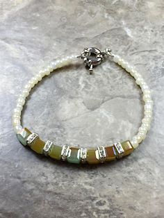Green multi color cube bracelet made with a green cube crystal and cube rondelle complement with white seed beads and sterling silver hook.