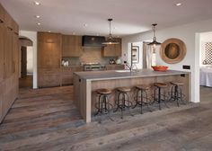 Neutral wood cabinets, flooring, and bar brings a relaxed rustic touch into this sophisticated, contemporary kitchen. A long bar is paired is paired with metal and wood stools for plenty of seating. Recessed ceiling lights illuminate the bright white space.